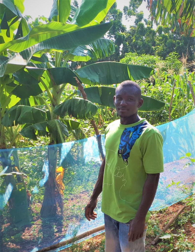 mAN STANDING NEXT TO CORN IN BLUE NET